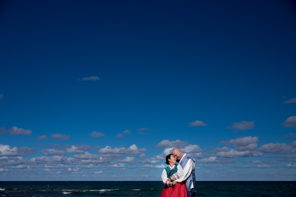 This is a portrait from Joohee + Joel's wedding up in Tobermory.   We had just finished the civil wedding ceremony, right on the water at Joel's mothers property, and paused for a few pictures.   I love the colours in this picture, from the traditional Korean hanbok to the brilliant blue of the sky.