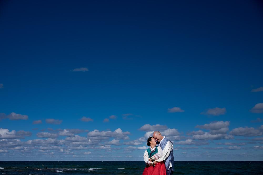A wedding portrait of Joohee + Joel wearing their traditional Korean wedding attire on the waterfront in Tobermory.