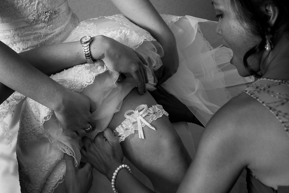 Bridesmaids help with putting on the garter before Jennifer + Ian's wedding in Waterloo.