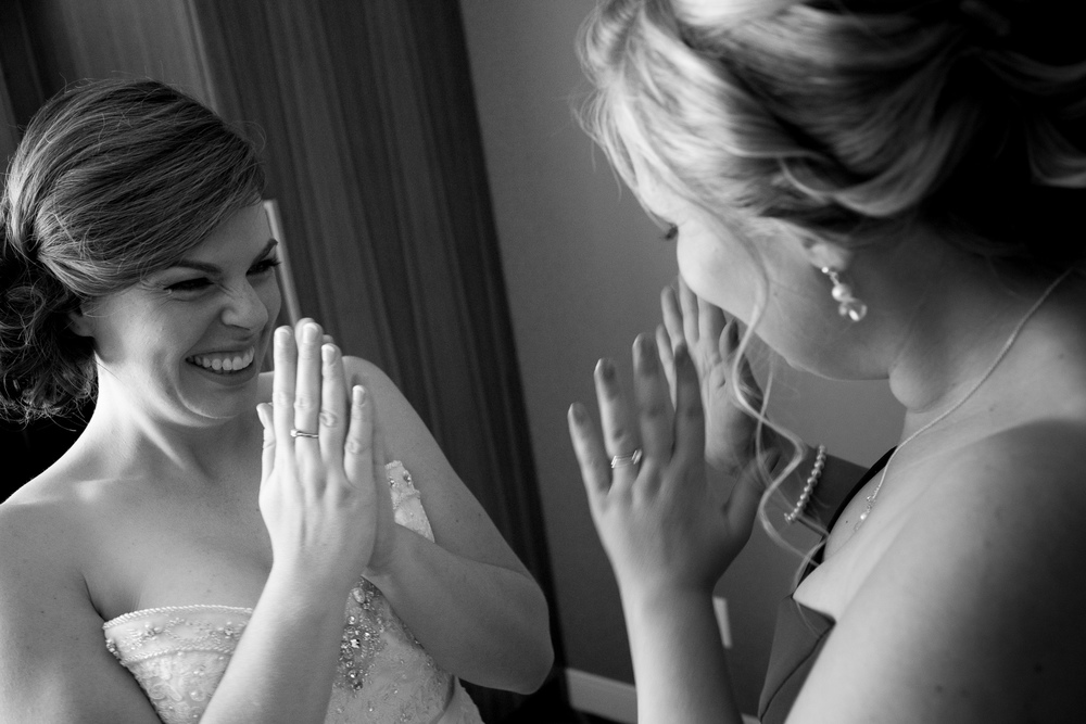 Jennifer and her maid of honour share a moment of excitement once the wedding dress is on and everything starts to feel real before her wedding in Waterloo.