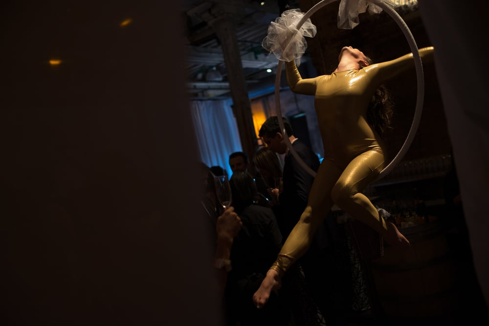 An aerial acrobat serves champagne during a wedding reception at the Fermenting Cellar in the Distillery District in Toronto, Ontario.