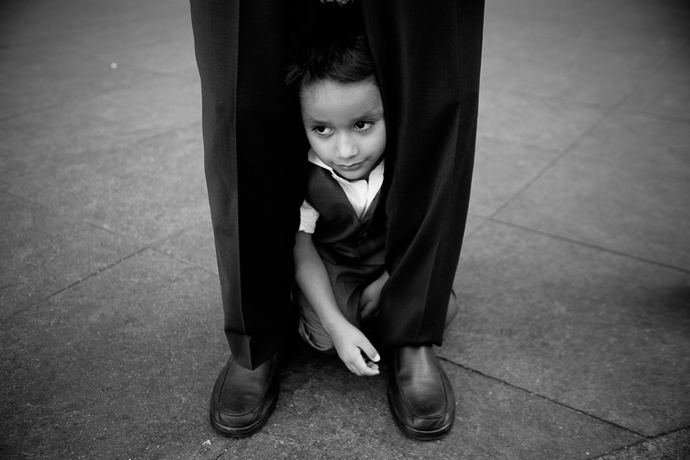 The nephew hides between his dad's legs while waiting to have his portrait taken at the wedding.