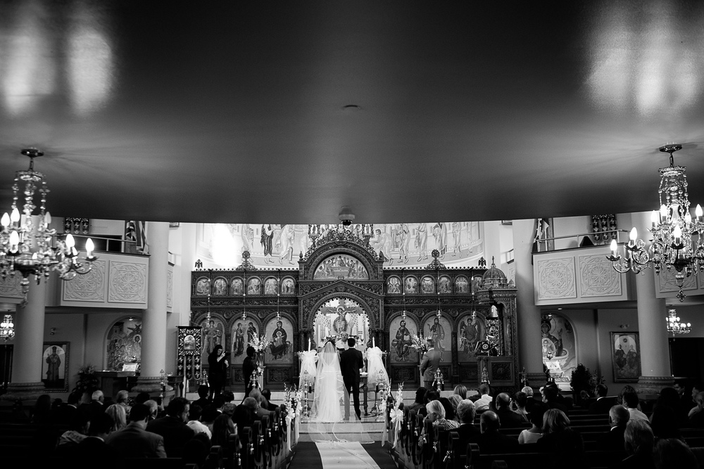 A photograph during their wedding ceremony at a Greek Orthodox Church.
