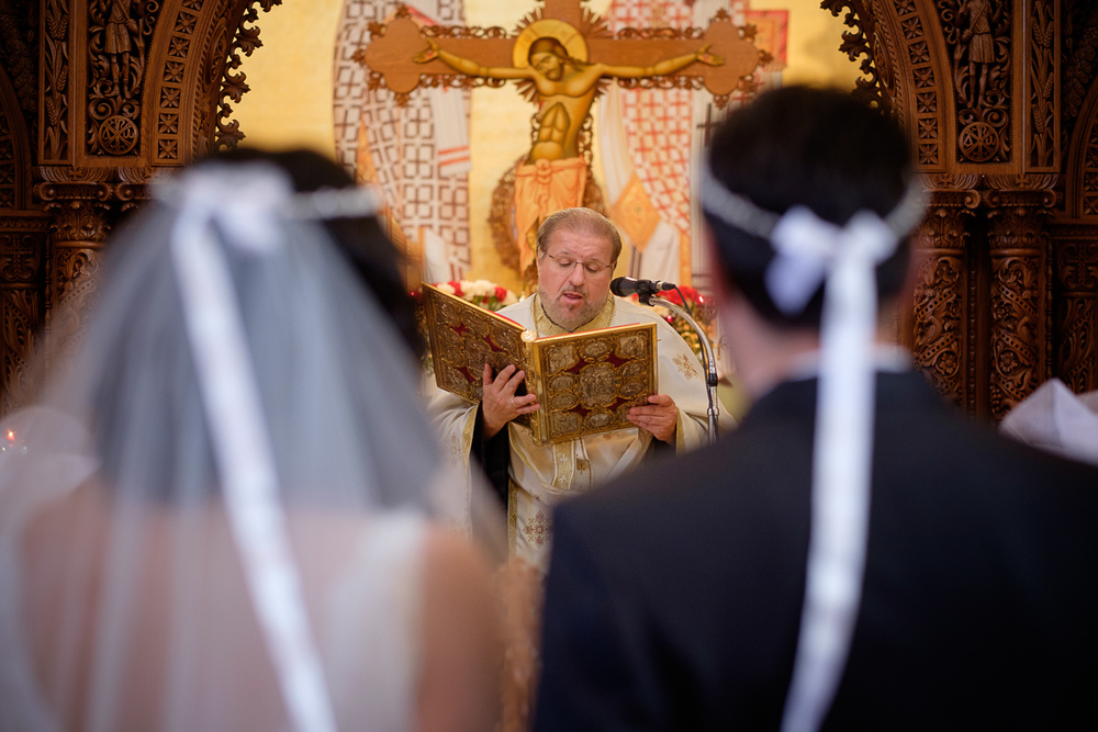The priest blesses the couple during their wedding ceremony at a Toronto Greek Orthodox Church.