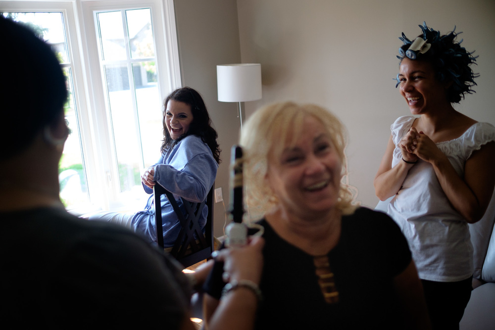 Laura and her family share a laugh as they have their hair and makeup done before her wedding at the Paletta Mansion in Mississauga.