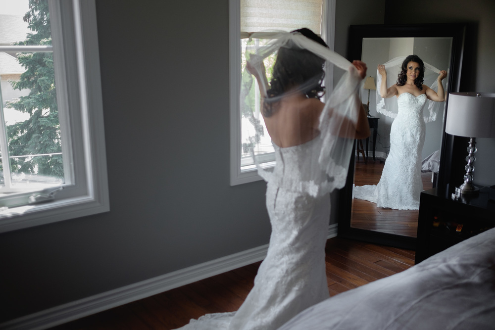 Laura adjusts her veil before her wedding in Mississauga at the Paletta Mansion.