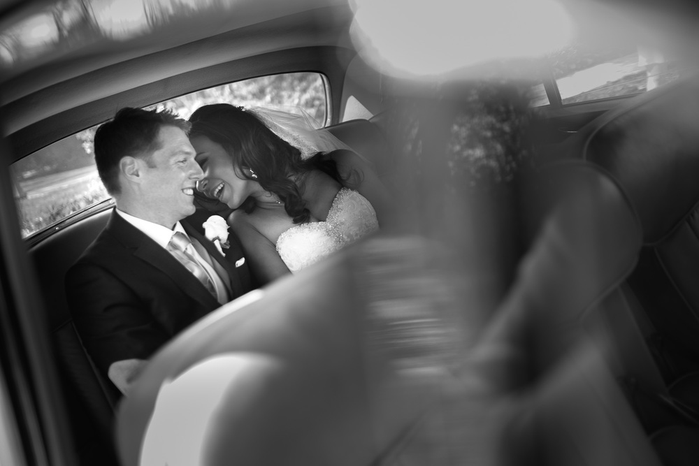Laura and Chris share a moment during wedding portraits in a vintage car at the Paletta  Mansion.