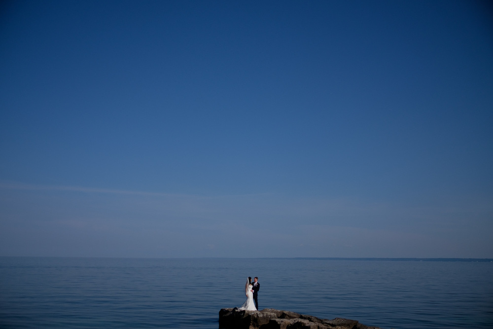 Laura + Chris pose for a dramatic wedding portrait on the shores of Lake Ontario at the Paletta Mansion in Mississauga.