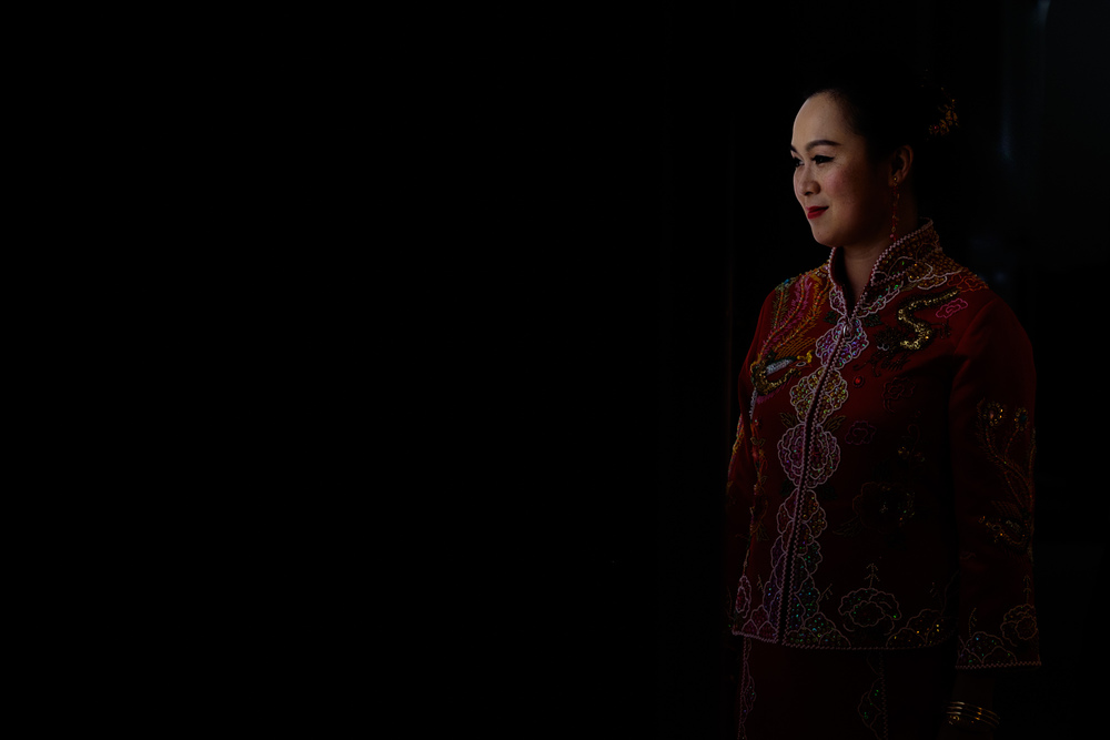 A window lit portrait of Jing in her traditional Chinese wedding attire before her wedding ceremony.