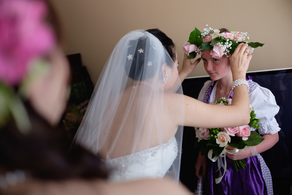 Jing adjusts the flower headpiece on her niece before their outdoor wedding ceremony.