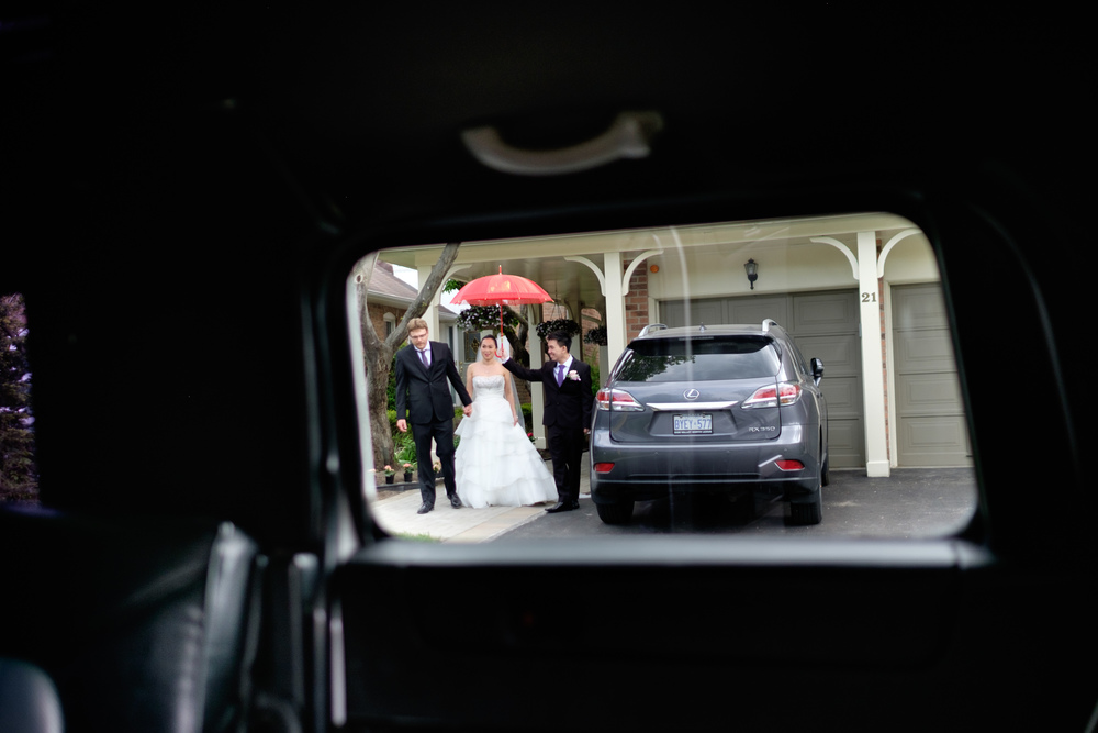 Jing is escorted to the limousine as she is covered by a red umbrella.