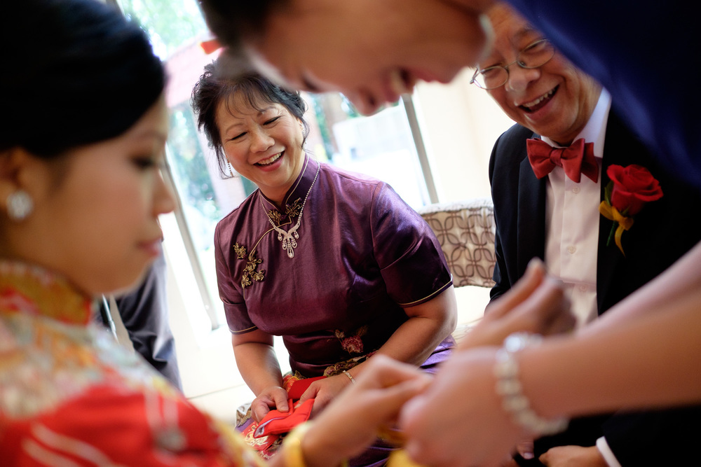 Jonathan's parents look on as Sherry tries on the jewelry they gave her during the traditional Chinese Tea ceremony.