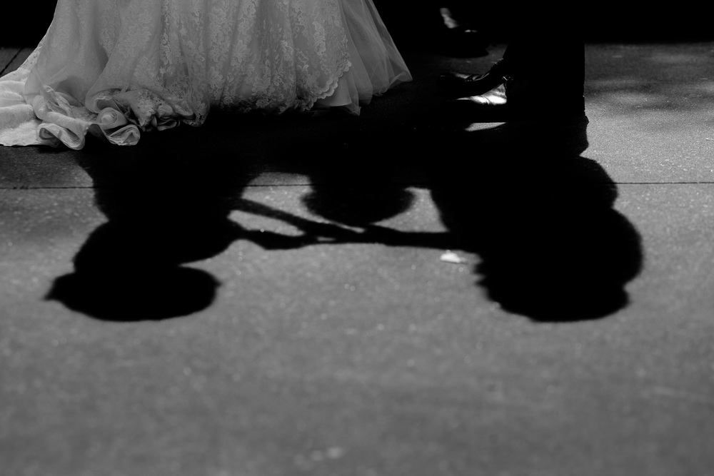 The shadow of the couple as they exchange rings during their outdoor wedding ceremony at the Columbus Centre in Toronto.