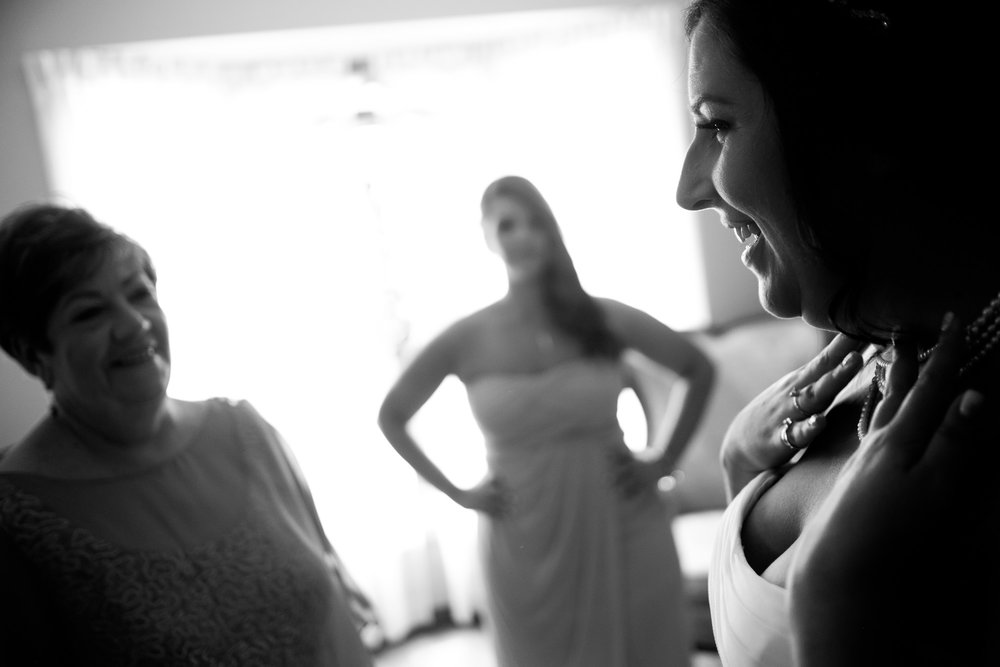 Melanie's mom looks on as she puts the finishing touches on her wedding dress and jewelry before her wedding in Toronto.