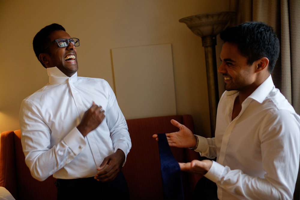 Trevin shares a laugh with one of his groomsmen as they get dressed in their suite at the Hyatt Yorkville in Toronto before the wedding at the Art Gallery of Ontario.