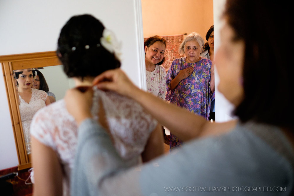 The brides family looks on as she puts her wedding dress on before her wedding at the Ancaster Mill in Ancaster, Ontario.