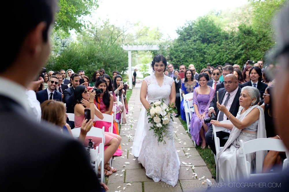 The bride walks down the aisle during her outdoor wedding ceremony at the Ancaster Mill in Ancaster, Ontario.