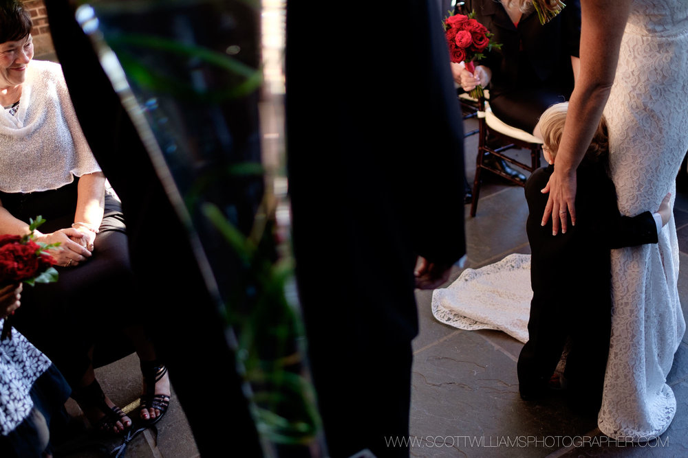 A photograph of the ring bearer holding onto the bride during the wedding ceremony during a smaller, intimate wedding at Langdon Hall in Cambridge, Ontario.