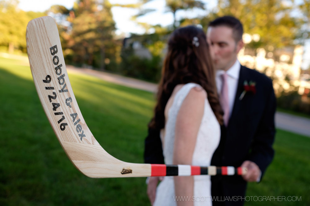 A wedding portrait of a couple posing with a custom hockey stick in front of Langdon Hall in Cambridge, Ontario.