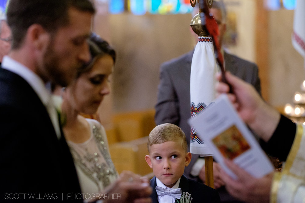 The ring bearer looks on as Christina & Tim revive a wedding blessing during their Ukranian wedding ceremony in Toronto.
