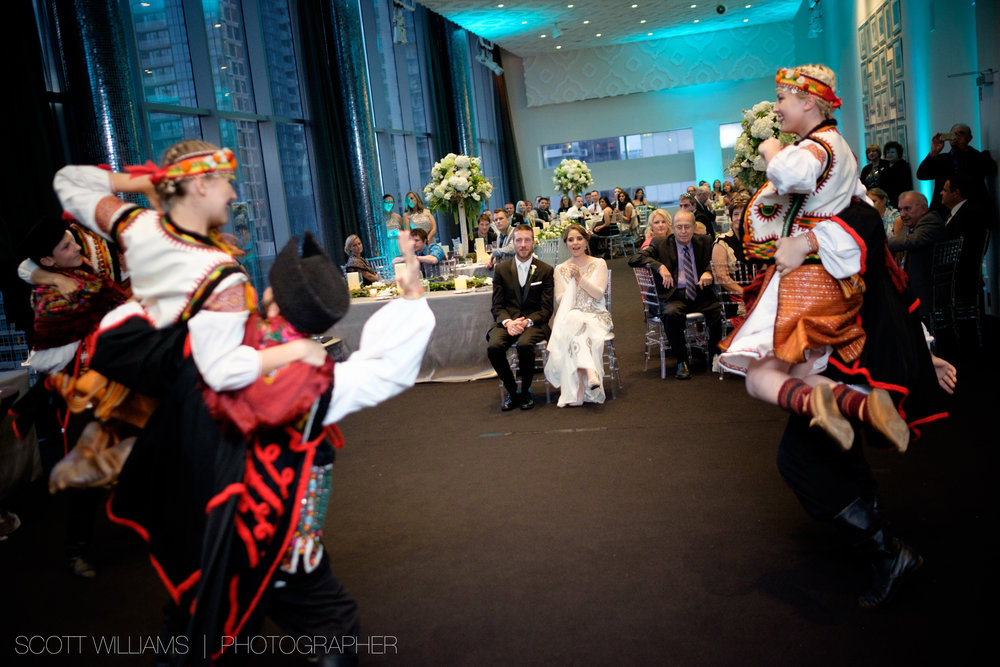 Christina & Tim look on as traditional Ukrainian dancers perform at their wedding reception at Malaparte in Toronto.