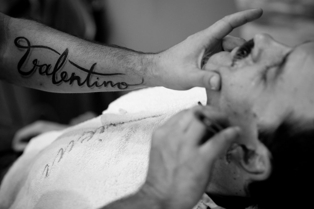 A groomsmen gets a straight razor shave before an intimate downtown wedding at Canoe Resteraunt in Toronto.