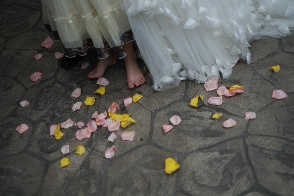 A barefoot flower girl stands amongst flower petals at a Cambridge wedding ceremony.