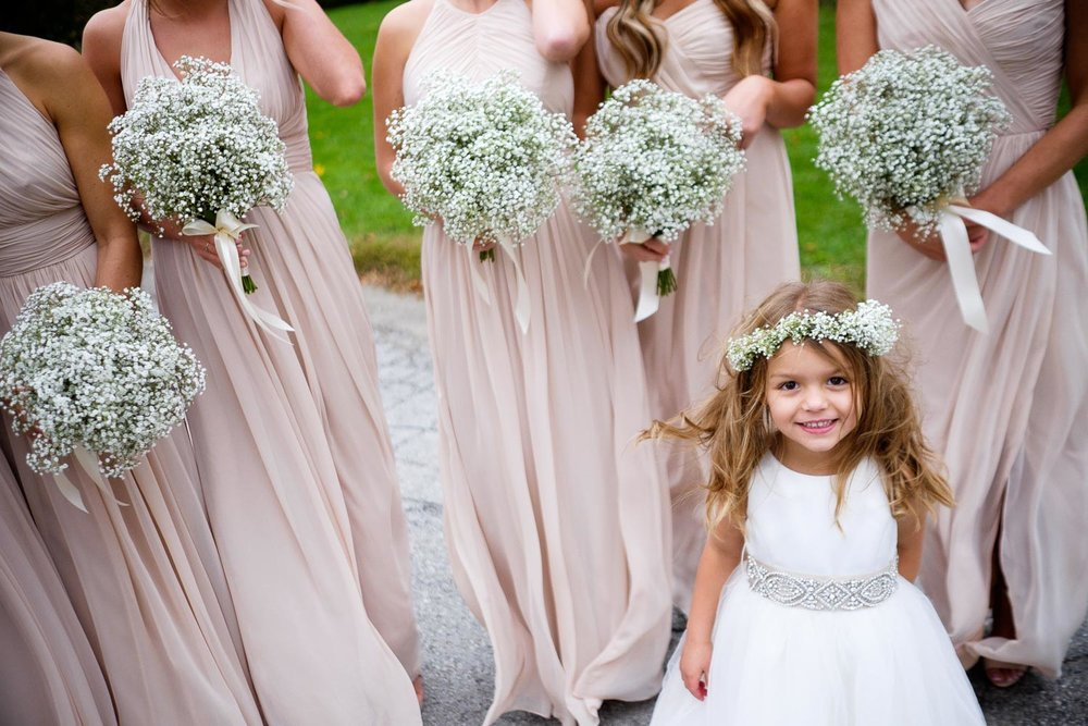 A young flower girl smiles for the camera as she waits with the bridesmaids during wedding portraits in Toronto.