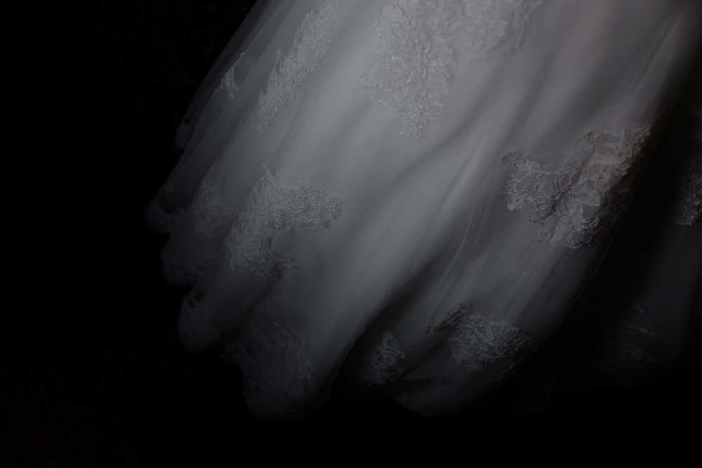A black and white detail photograph of the wedding dress.