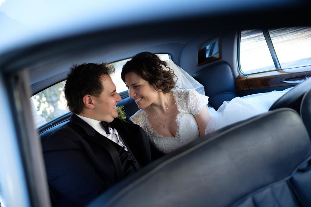 A wedding portrait inside a classic limousine at Graydon Hall in Toronto,