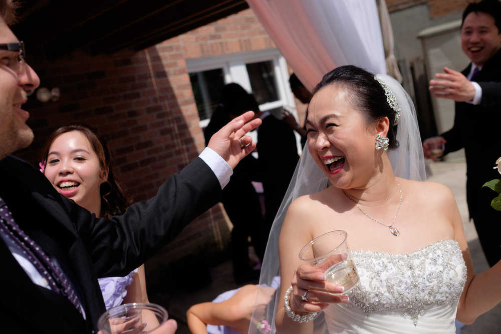 Love the joy and laughter on Jing's face after their backyard wedding ceremony in Toronto.