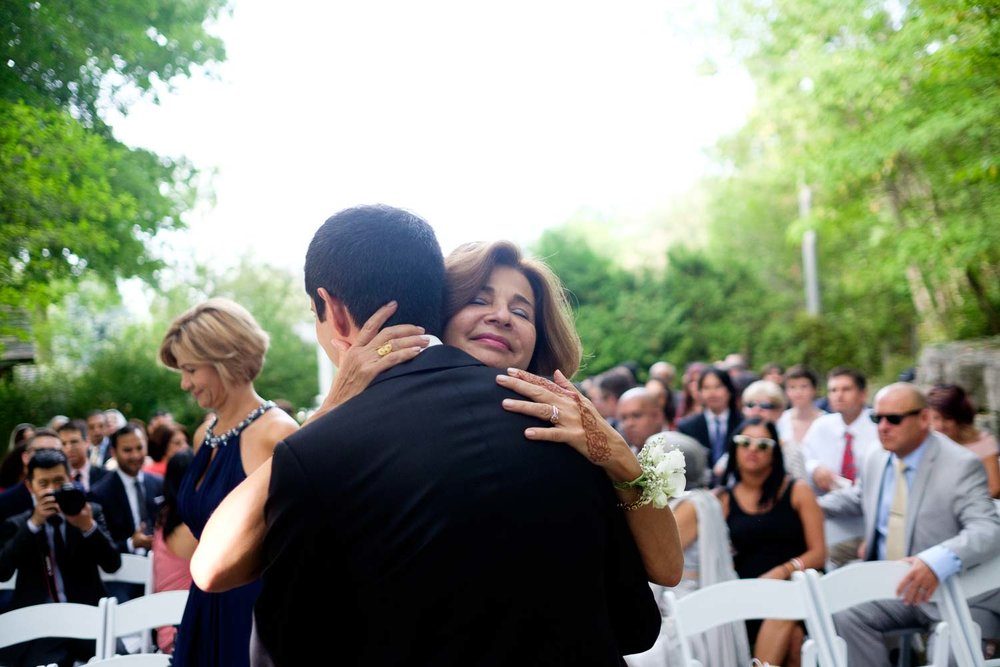 A mother embraces her son during the outdoor wedding ceremony at the Ancaster Mill in Ontario.