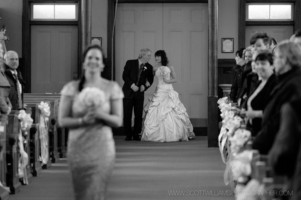 The bride and her father share a moment before walking down the aisle during her wedding in North Bay, Ontario.