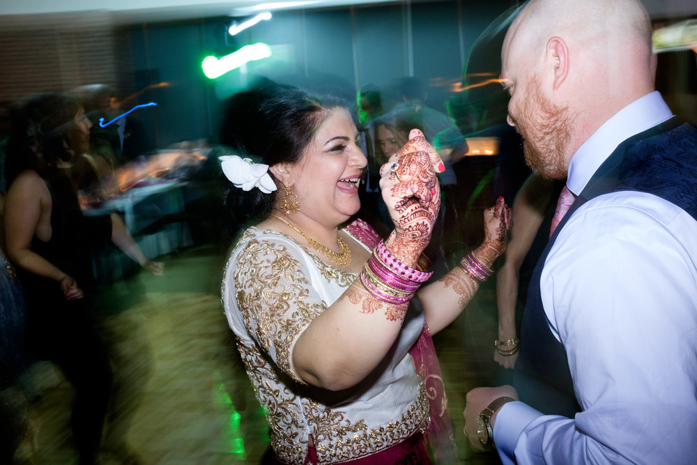 Noor and John party it up on the dance floor during their wedding reception at the Toronto Reference Library.