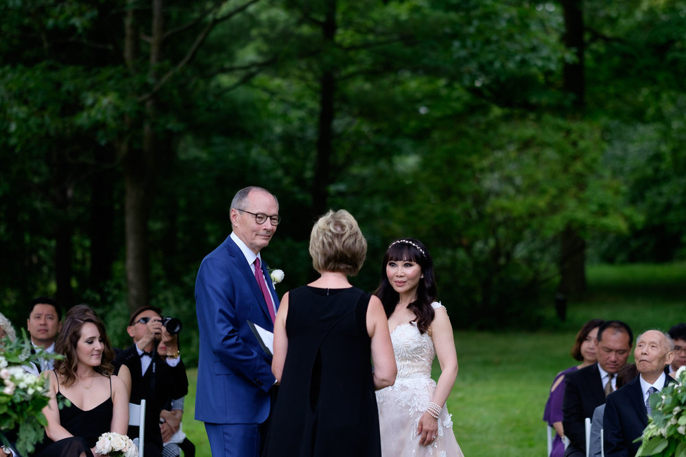 Robert and Teresa exchange wedding vows during their intimate outdoor wedding ceremony at Langdon Hall in Cambridge, Ontario by Scott Williams.