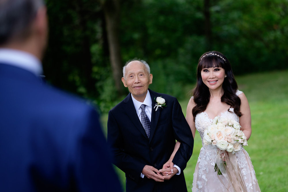 Teresa walks down the aisle in the arms of her father during their outdoor wedding ceremony at Langdon Hall in Cambridge, Ontario by Scott Williams.