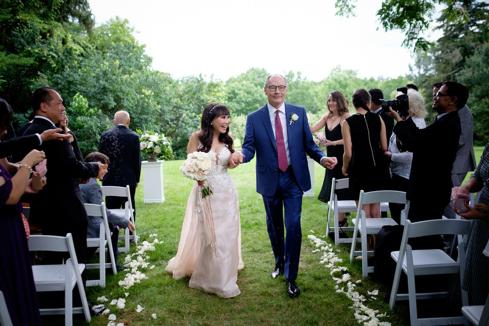 Teresa + Robert dance their way back down the aisle after exchanging wedding vows during their outdoor ceremony at Cambridge's Langdon Hall.  Photo by Scott Williams.