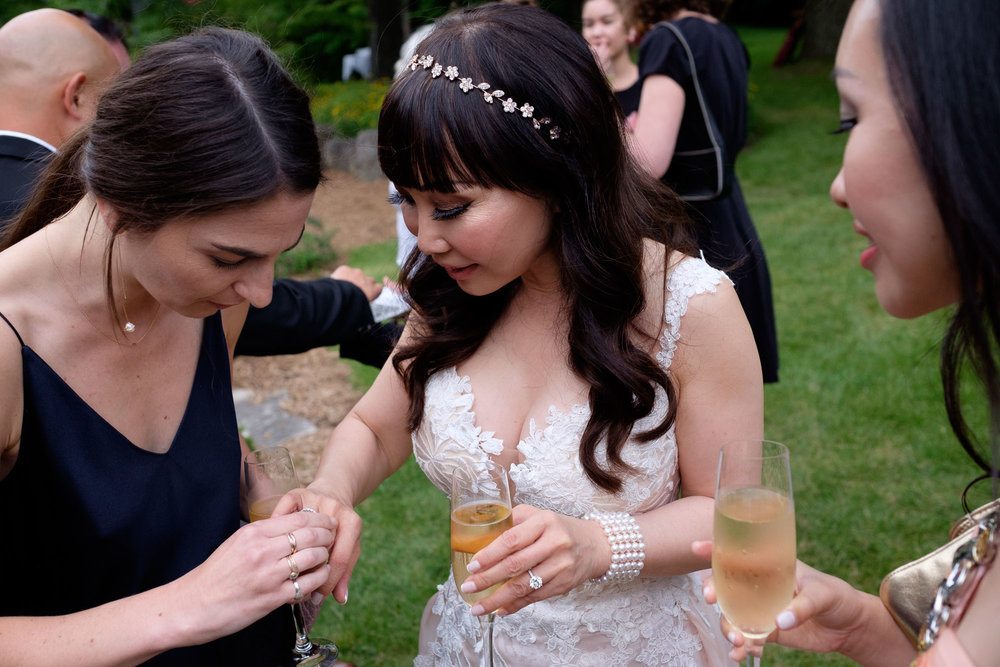 Guests check out Teresa's wedding ring during their cocktail hour at Langdon Hall in Cambridge, Ontario by Scott Williams.
