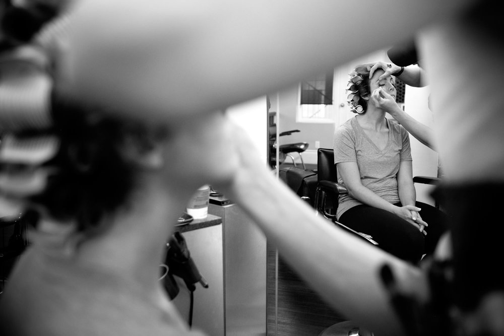 A black and white photograph of Jennifer having her make up applied before her wedding at the Markham Museum.