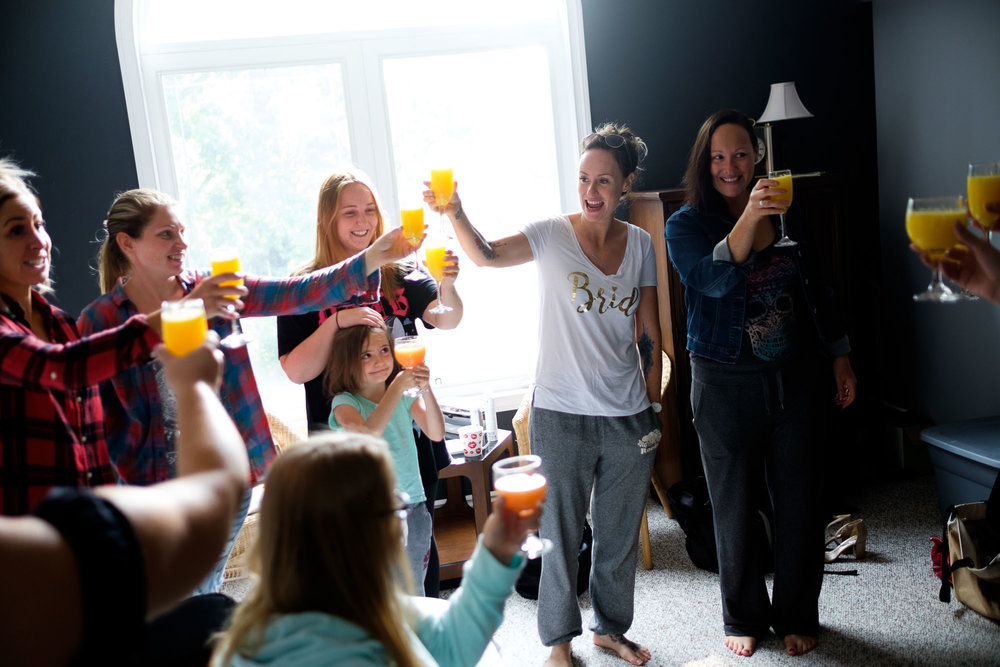 Kristin and her bridesmaids share a toast in the morning before her wedding as they get ready with hair and make up in Barrie, Ontario by Scott Williams.