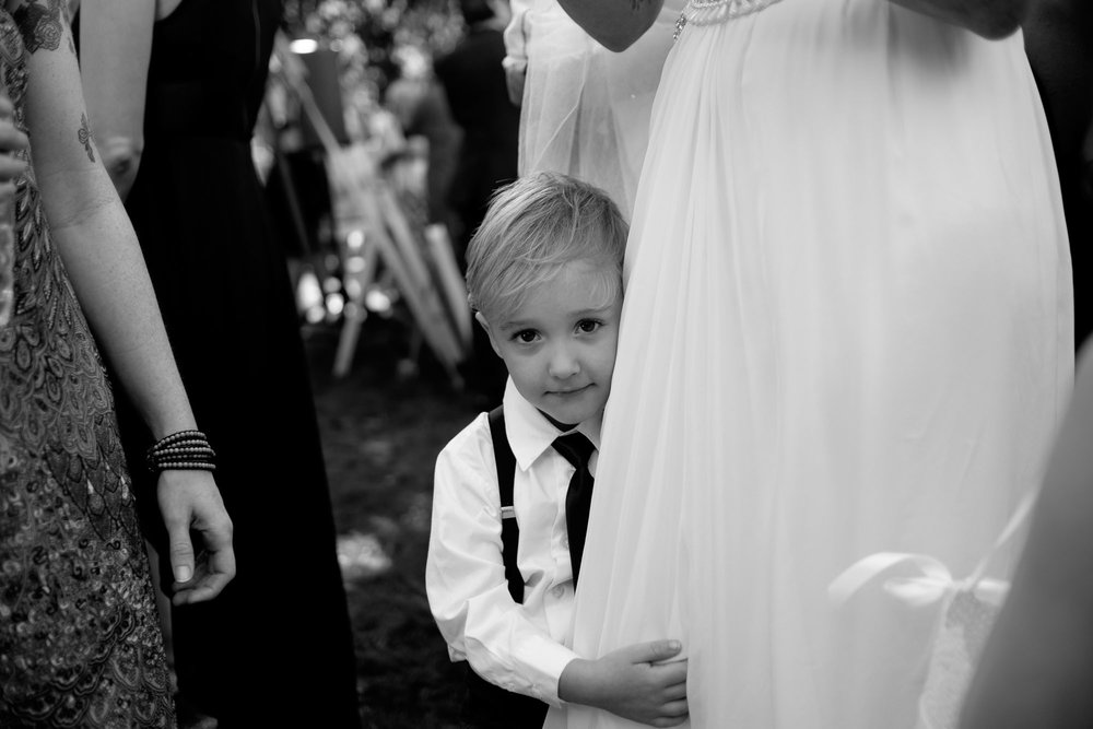 The brides son clings to her wedding dress during cocktail hour at their backyard wedding in Barrie, Ontario.  Photograph by Scott Williams.