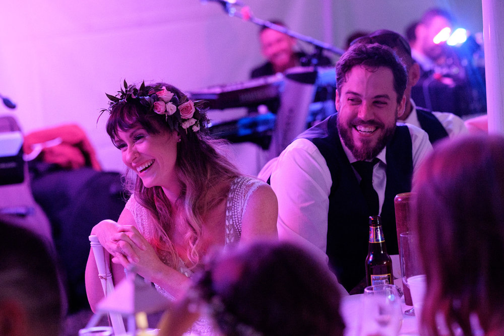 Kristin and Adam laugh during a toast at their backyard wedding reception in Barrie, Ontario.  Photograph by Scott Williams.