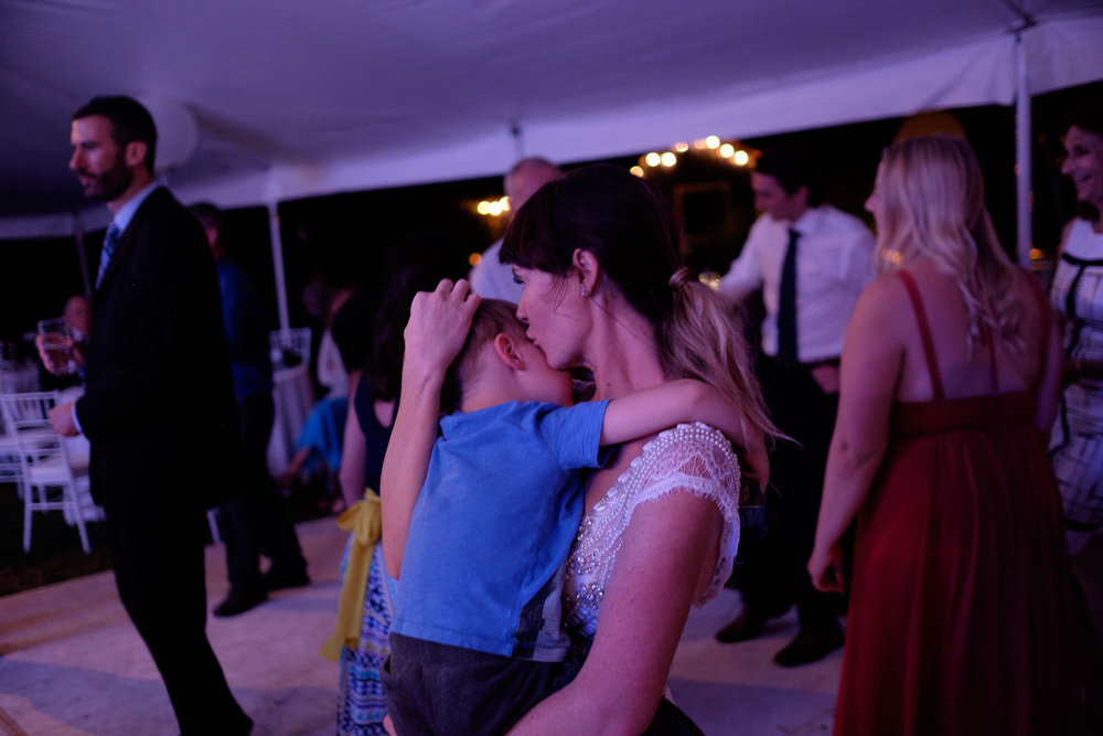 The bride and her son share a moment on the dance floor during the wedding reception in her backyard in Barrie, Ontario.  Photography by Scott Williams.