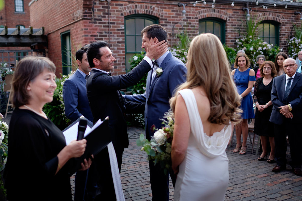 Enrico shakes hands with Cindy's son during their wedding ceremony at Archeo in the historic Distillery District in Toronto.