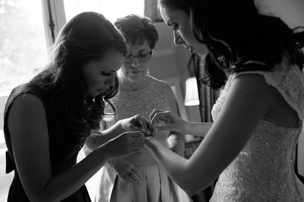 Amanda is helped with her bridal jewelry by her mother and sister in the suite at Langdon Hall.