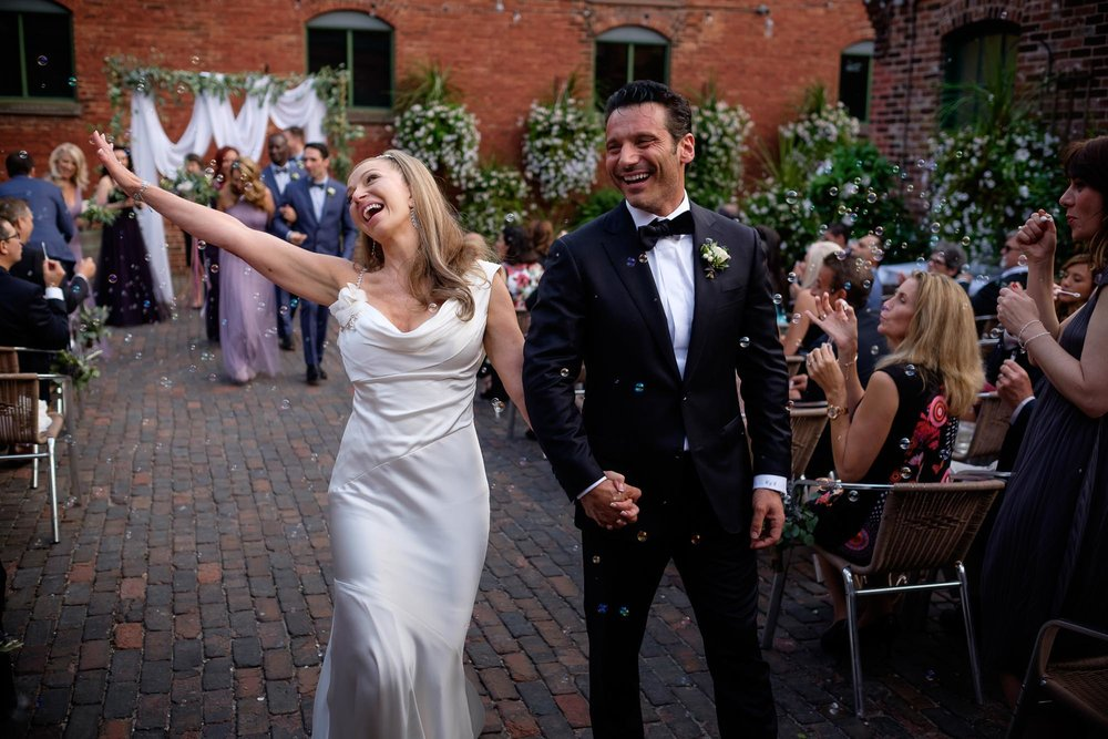 the bride and groom dance their way down the aisle after their wedding ceremony at Archeo in Toronto's Distillery District.