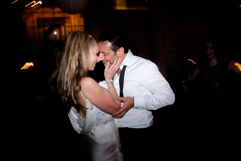 The bride and groom dance during the reception at their wedding at Archeo in Toronto's distillery district.