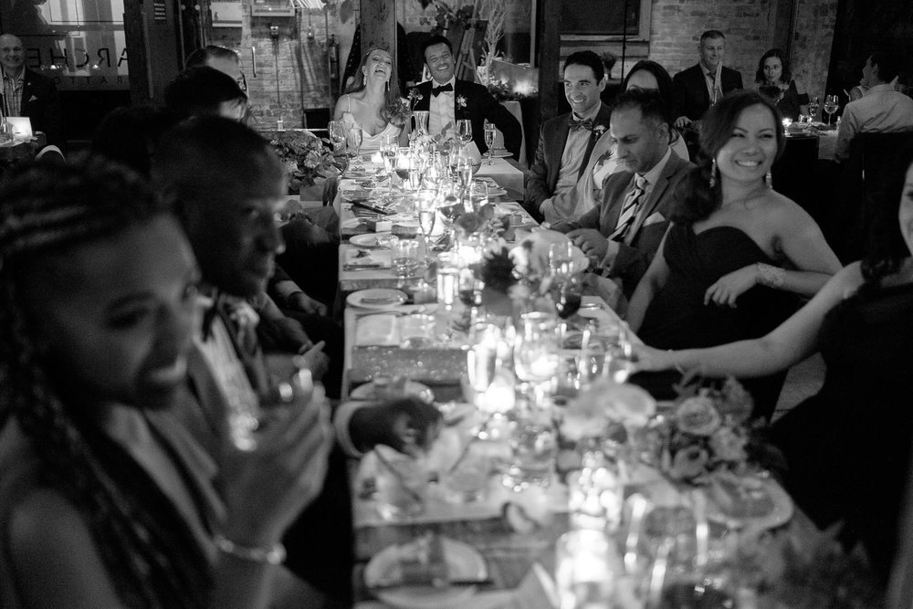 The bride and groom react to a wedding toast during their wedding reception at Archeo in toronto .