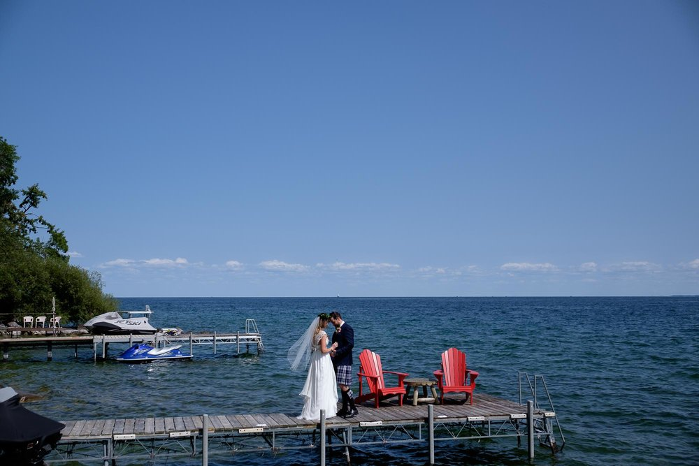 the bride and groom enjoy their first look on a dock on Lake Simcoe before their backyard wedding.