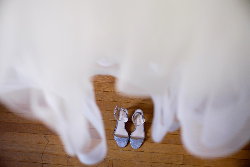 A wedding detail photograph of the brides dress and shoes from a wedding at the Hart House in Toronto, Ontario.